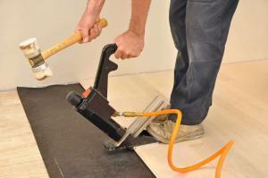 A man using a flooring nailer.