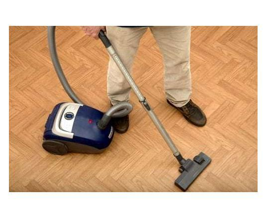man vaccuming hardwood floor