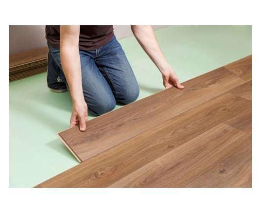 person installing wood flooring