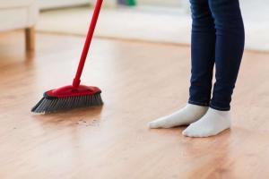 woman sweeping hardwood floor